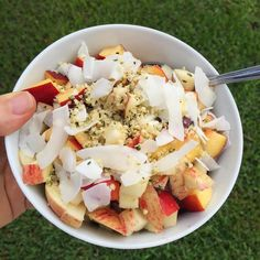 A big bowl of fruit for breakfast. Underneath the apple and nectarine is banana blueberries and Acai and all topped with coconut and hemp seeds.