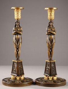 """Une paire de bougeoirs """"retour d'Égypte"""" en bronze patiné et doré.Sur une base circulaire en bronze patiné, décorée de deux chiens chassant un cerf, se dresse un piédestal..."""