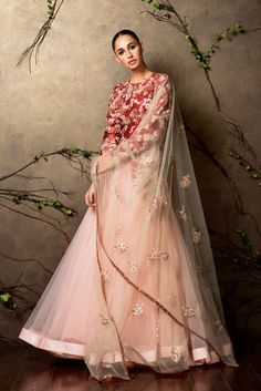 A pompeien red raw silk jacket with cluster of peach pearl and almond beige embroidery. A voluminous peach pearl tulle lehenga is worn over it. This is coupled with a delicate hand embroidered tulle dupatta. Sales@shyamalbhumika.com www.shyamalbhumika.com