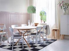 Ljus matplats med ovalt bord med vit bordsskiva och ben i björk. Här med vita stolar med grå stolsdynor.