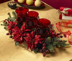 Beautiful poinsettia flowers and berries color this silk plant. Three beautiful red candle holders are nestled into this decorative table accessory. Materials: Polyester, plastic, iron wire, glass Pla