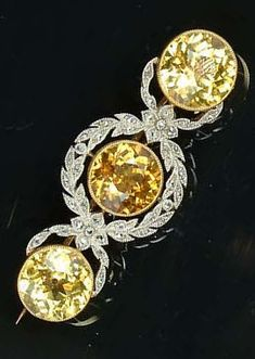 An Edwardian yellow sapphire and diamond bar brooch, circa set with three circular-cut yellow sapphires, the centre stone within a millegrain-set rose-cut diamond garland, London & Ryder leather case, length Edwardian Jewelry, Antique Jewelry, Vintage Jewelry, Vintage Brooches, Royal Jewelry, Jewelry Box, Fine Jewelry, Jewellery, Diamond Bar
