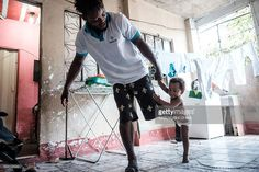 Popole Misenga (L), 24, a refugee judoka from the Democratic Republic of Congo, plays judo with his one-year-old son Heliasin at home in Rio de Janeiro, Brazil, on April 14, 2016. Misenga is a strong candidate for the newly created Refugees Olympic Athletes team for the Rio 2016 Olympic Games. The Congolese athlete --who has been split from his family due to the civil war in Congo since he was ten years old-- decided to stay in Brazil during the World Judo Championshio in 2013 together with…