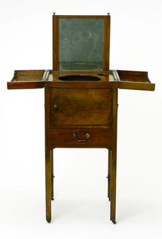 """1787 British Shaving table at the National Maritime Museum, London - From the curators' comments: """"This shaving table is said to have belonged to Horatio Nelson. It is veneered with mahogany and the two handles on either side indicate that it would most likely have been used as travelling furniture. The top opens out to reveal a cut-out for a bowl and glass (now missing) and there is a swing mirror at the back of the cabinet."""""""
