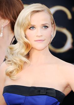 """Reese Witherspoon channeled an old-Hollywood movie star at the Oscars this year with Veronica Lake-esque waves, which were made modern with brushed out, loose curls instead of stiff and cramped coils. """"It's pure beauty and glamour and just perfect for a special occassion,"""" said Campora, who was responsible for giving Witherspoon the vintage-inspired mane. """"Hair pulled all to one side shows off the neck and earrings, and at the same time it both opens and frames the face.""""   - ELLE.com"""