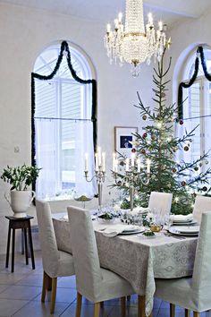 Salin kolmimetriset holvikaari-ikkunat ovat juhlavat. Aattona kristallikruunuun sytytetään kynttilät. Pellavaliina, kukat ja vanhat Arabian astiat luovat jouluun juhlavaa tunnelmaa.