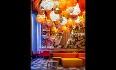 Generator Hostels Barcelona, Spain More than 300 lanterns in the hotel's lobby set the stage for a party atmosphere, along with a mix of wallpaper, reclaimed wood panels, floor tiles, and orange furnishings.