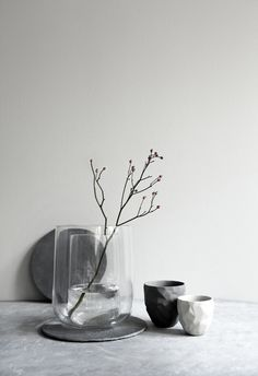 Flower to break up the space with the products. Grey tones used for candles and ceramics.
