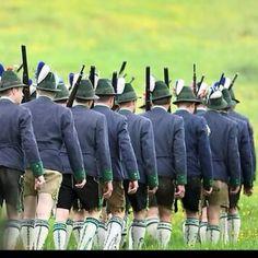 Teilnehmer des Patronatstages der bayerischen Gebirgsschützen ziehen über eine Wiese bei Ohlstadt in Oberbayern.