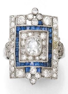An Art Deco diamond, sapphire, platinum and gold ring. The ring designed as a rectangular plaque centring a cushion cut diamond surrounded by calibré sapphires and small diamonds, mounted in platinum and white gold. #ArtDeco #ring