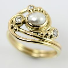 Elegant wrapping ring of gold with pearl and diamonds. The gold flows in soft lines around the finger and a baroque freshwater pearl. A bunch of bubbles play between the lines - some with glittering diamonds!