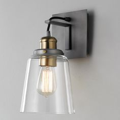 "Vice Wall Sconce Simplicity is beautiful with this Vice Wall Sconce with clear glass. Form and function combine to make this perfectly appropriate for decor ranging from transitional to modern. Available in Brushed Nickel, Polished Nickel, Bronze, or Graphite with Antique Brass accents. Rear backplate is 4 3/4"" square. Front backplate is 5 1/2"" square. (11.75""Hx6""Wx7.5""D)"