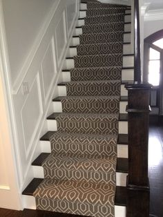 Beautiful stairway with wainscoting paneled half wall and geometric stair runner in taupe and ivory. Geometric Stair Runner, Home, Modern Stairs, Entrance Foyer, Foyer Decorating, Stair Runner, Dining Room Wainscoting, Stairs, Stairways