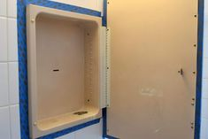 Painter's tape was applied around the frame of the rusty medicine cabinet to protect the wall tile and mirror frame. - The Handyman's Daughter