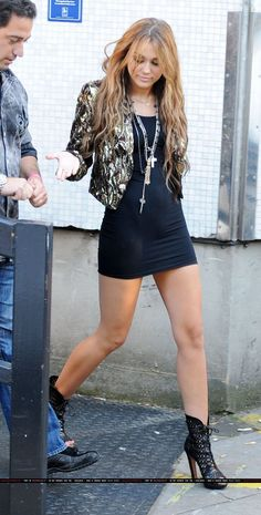 Miley Cyrus looking amazing in a little black dress and little boots. Fantastic legs.