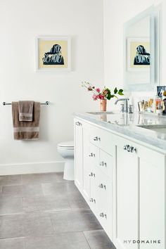 All-white bathroom with flowers, small art, and brown hand towels
