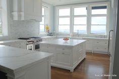 White Marble Kitchen by Stay at Homeista. Love the Calcutta Oro counters, Christopher Peacock walnut cabinets, and the view!