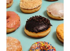 Chocolate frosted doughnut sits on a blue table surrounded by other iced doughnuts from Glory Hole in Toronto.