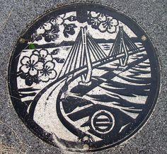 draincover on Ikuchijima, Hiroshima Prefecture, and it depicts the Tatara Bridge which connects Ikuchijima with Omishima