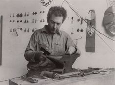 Calder with jewelry hanging on the wall in his studio at 7 Villa Brune, Paris, November 1930 Photograph by Thérèse Bonney