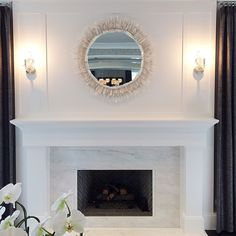 Stunning living room fireplace boasts a white marble surround and a contrasting gray herringbone firebox under a white mirror illuminated by nickel and glass sconces