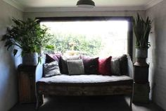 A vintage sofa-cum-daybed overlooks the garden flanked by two metal pots to create a modern take on a Victorian tableau.