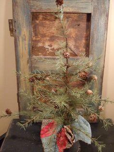 Prim Christmas...twiggy pine with old quilt skirt...worn door.