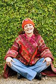 Portrait of a young woman sitting cross-legged on footpath and smiling - Stock Photo