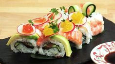 Salmon sushi roll topped with sea bass, avocado, salmon roe and prawns. Recipe.