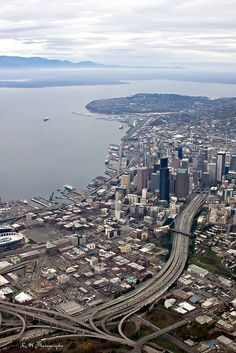 Aerial view of Seattle. You can see the stadium where the world champion Seattle Seahawks play, and I-5 snaking through downtown. Elliott Bay is to the left. Photo by Kevin Miller