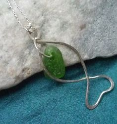 This little fishy is made with hammered sterling silver and has a a pretty piece of green sea glass hanging in his body. Hand made by Cathie Palmer SOLD #SeaglassFishPendant #SeaglassPendant