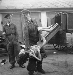 """An undertaker in the Warsaw ghetto's Jewish cemetery on Okopowa Street lifts the body of a woman for Heinrich Joest to show him how little it weighs.   Joest's caption reads: """"The dead were not heavy, as one corpse-bearer showed me - although I had not asked him to - in front of the buildings of the Jewish cemetery."""""""