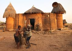 Benin - Boy and girl crushing grain enthusiastically in front of their house
