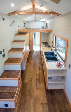 The kitchen includes hand-built birch cabinetry with soft-close drawers and cupboards, two large pantries under the storage stairs, a gas cooktop, and an apartment size refrigerator. A black granite sink sits in front of a large picture window.