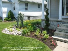 landscaped front yard and porch with brick walkway, flowering plants, and hardscaping