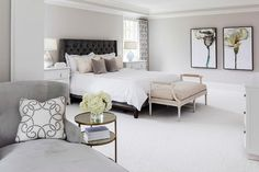 Chic gray bedroom features walls painted Benjamin Moore Balboa MIst lined with a dark gray velvet tufted bed dressed in white and lilac bedding flanked by white dressers as nightstands place in front of windows dressed in white and gray scroll curtains.