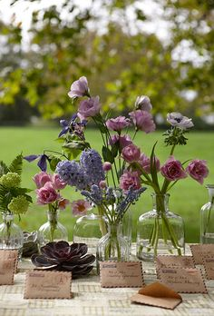 """Brides.com: Unique Wedding Flower Ideas. Enchanting Tableau Your wedding's a little bit country, a little bit...global? Combine the two with a charming seating-card station that pairs vintage mini air-mail envelopes with a casual grouping of posies. Place stems like viburnums, double tulips, hyacinths, """"Tote"""" lilies, clematises, lisianthus, umbrella ferns, anemones, gomphrenas, muscari, and succulents in assorted glass bottles for a fresh-from-the-garden look.Bud vases, The Home Port…"""