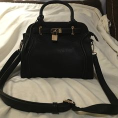 Melie Bianco  Madison Lock and Key handbag Madison lock and key handbag. Black with brown trim along the seams. Gold hardware Depth 7in width at top 9in  width at base 101/2 in hight from top of handle to base is 14 in. Gold with brown polka dot silk lining. One zippered inner pocket and 2 side pockets for cell phone, compact,lipstick ect....  Has shoulder strap for cross body/shoulder option.  Excellent condition!! No Damage, marks or stains. Gorgeous classy handbag. Melie Bianco Bags