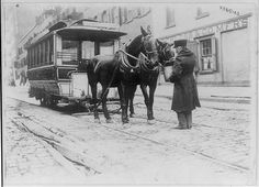 """A driver, feeding/watering his horses, that are pulling a horse-drawn street car, New York City c.1908 - Caption description: """"Conductor watering horses"""". The street car named the, """"Chambers Street Ferry"""", is indicated by signage on the front of the vehicle. ~ {cwlyons} ~ (Image: LOC - Bain Collection)"""