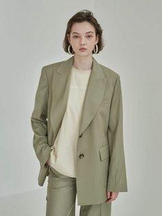 Peaked collar green blazer by Mohan. Afflink.