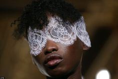 Hidden beauty: Models walked the runway behind lace blindfolds teamed with blood red lips...