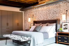 Brick wall in bedroom with gray and white bedding