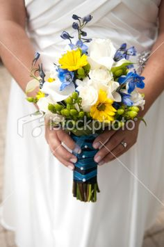 The bridesmaids' bouquets will be a loose, natural clutch of white scabiosa, white fringed tulips, blue cornflowers, blue-purple muscari, yellow lisianthus, yellow freesia, green blupleurum wrapped in a thin piece of burlap fabric with the stems showing.