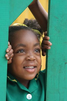 Photograph of Jamaican school girl looking through the fence of her school - Jamaica - Central America  by www.traveladventures.org