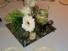 Alternate the centerpieces for your guests tables. Here is a 3 tiered vase variety with white rose, gerbera daisies, button and spider mums. A  tied ribbon in your accent color adds a nice touch. Very lovely.