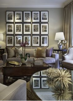 Marvellously sumptuous and elegant living room in soft greys, old gold and smoky mauve beautifully accessorised with symmetrical photograph arrangement cleverly reflected in the glass table top.