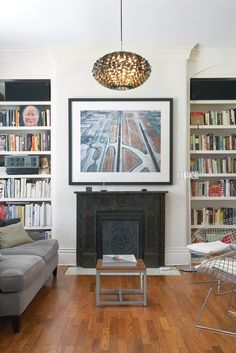 The living room in the original house has Victorian details, but the furniture—vintage Bertoia chairs, a Gloss floor lamp by Pablo Pardo, and a Norm 03 Steel Pendant Lamp by Normann Copenhagen—brings the look up to date. Photo by: Noah Webb Victorian Fireplace, Faux Fireplace, Fireplace Surrounds, Beach Fireplace, Fireplace Outdoor, Limestone Fireplace, Small Fireplace, Fireplace Mirror, Concrete Fireplace