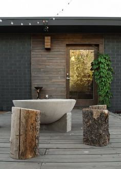 concrete outdoor bath, delicious tree log stumps as seating making an open amphitheater effect and that DELICIOUS gold wall just visible through the door... love the house siding so cute.