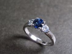 Blue sapphires engagement ring is set in 14K white gold. The center stone, a 5mm round brilliant cut natural blue sapphire is set in a four prong