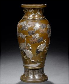 A large bronze baluster vase Meiji Period Inlaid with a bold design of cranes standing and flying about flowering cherry trees, clumps of peonies and wild flowers beside a stream, in silver, copper and shakudo takazogan with gilt details, the neck applied with two gilt ho-o birds among trailing kiri and the foot with inlaid silver stiff leaves, unsigned. Flowering Cherry Tree, Japanese Crane, Art And Craft Design, Japanese Porcelain, Incense Burner, Japanese Beauty, Metal Crafts, Antiquities, Metal Art